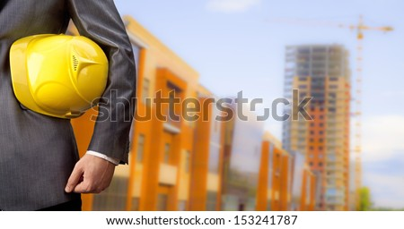 Copy space for inscription engineer yellow helmet for workers security on the background of a new high-rise apartment buildings evening sunset blue sky - stock photo