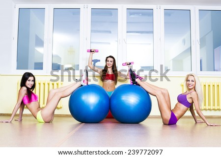 copy space for inscription Portrait of Three young adult sexy blond and brunette women Looking At Camera, doing sit-ups on exercise balls in gym on window reflection background Sitting on yellow floor - stock photo