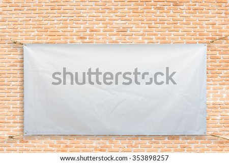 Copy space for text on disastrously white vinyl banner on brick background .Clipping path - stock photo