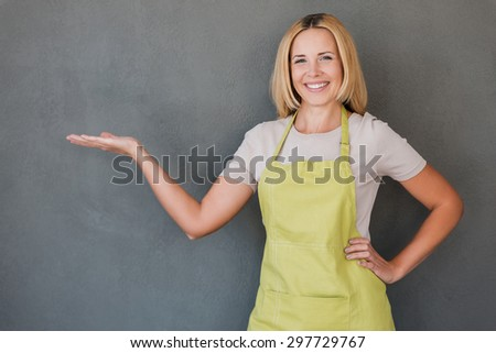 Copy space on her hand. Happy mature woman in green apron holding copy space and smiling while standing against grey background  - stock photo