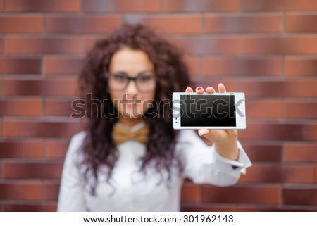 Copy space on her smartphone. Attractive young caucasian woman showing her mobile phone screen and smiling. - stock photo