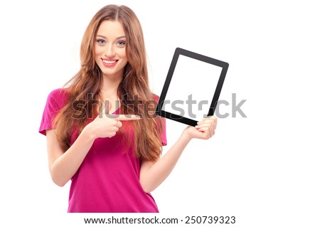 Copy space on her tablet. Confident young caucasian woman pointing her digital tablet and smiling while standing isolated on white - stock photo
