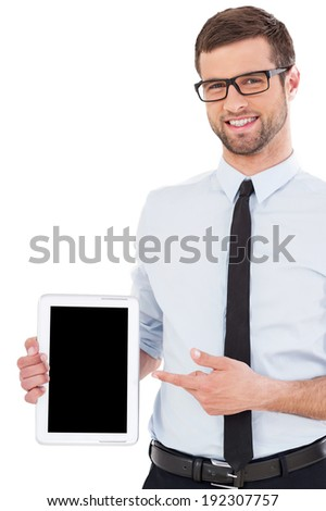 Copy space on his tablet. Cheerful young man in shirt and tie pointing digital tablet and smiling while standing isolated on white background - stock photo