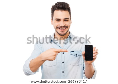 Copy space on his telephone. Cheerful young man showing mobile phone and smiling while standing against white background - stock photo