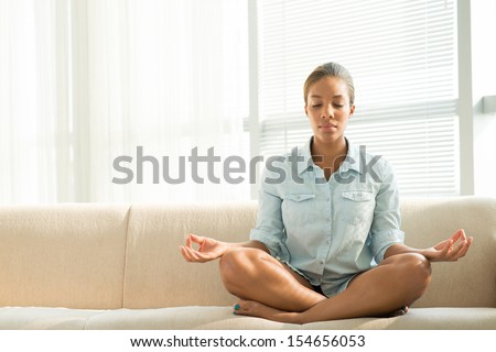 Copy-spaced image of a black woman meditating at home - stock photo
