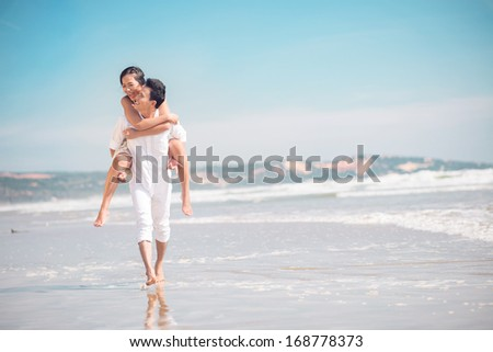Copy-spaced image of a cheerful young couple piggybacking on the beach  - stock photo