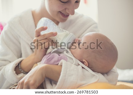 Copy-spaced image of a mother feeding her little baby from the milkbottle - stock photo