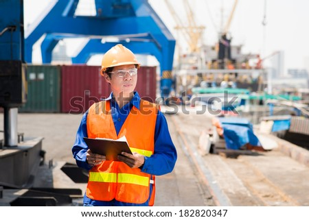 Copy-spaced image of a port superintendent with clipboard controlling the working process in the seaport - stock photo
