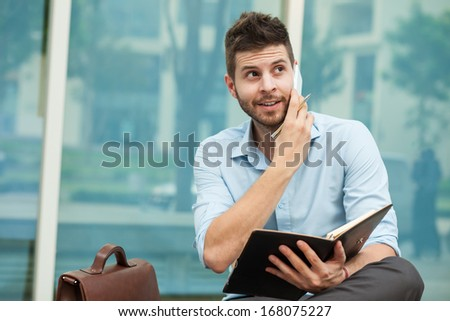 Copy-spaced image of a smiley businessman making a telephone call outside - stock photo