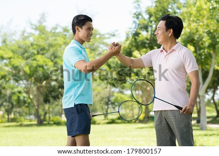 Copy-spaced image of a son and dad having friendly badminton competition and handshaking in the sign of friendship  - stock photo