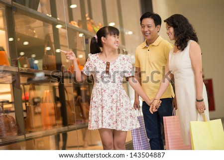 Copy-spaced image of a young daughter asking her mother to buy something in the store - stock photo
