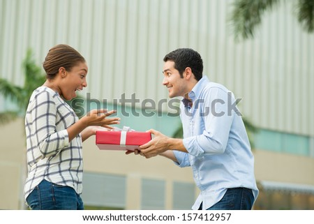 Copy-spaced image of an excited couple where a boyfriend presenting his girlfriend with a giftbox on the foreground - stock photo