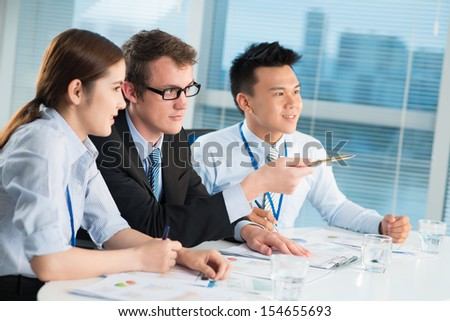 Copy-spaced image of businesspeople at the conference, the ceo pointing at something  - stock photo