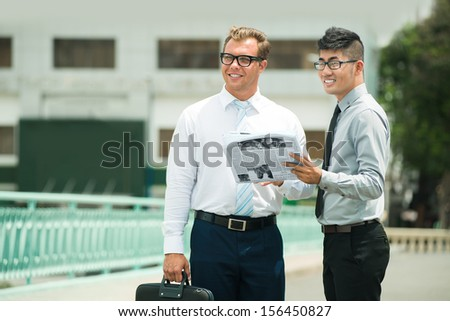 Copy-spaced image of international business colleagues standing and looking at something with interest with the newspaper in hands - stock photo