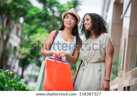 Copy-spaced image of young women having look at the mall with interest on the foreground - stock photo