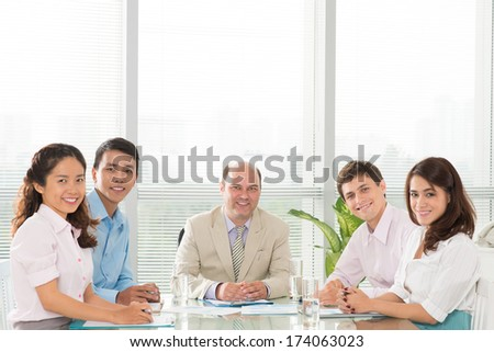 Copy-spaced portrait of a professional business team smiling and looking at camera at the office  - stock photo