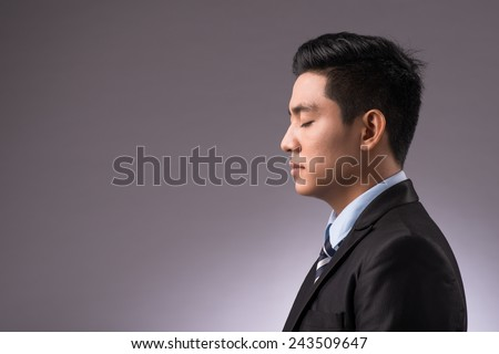 Copy-spaced portrait of a young businessman thinking over the business strategy over a black background. eyes closed focus entrepreneur - stock photo
