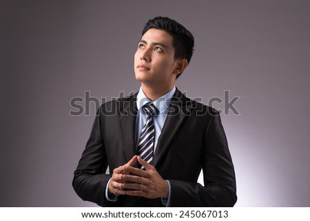 Copy-spaced portrait of a young businessman thinking over the business strategy over a gray background. Asian handsome entrepreneur focus looking up - stock photo