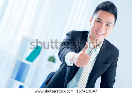 Copy-spaced portrait of a young financial consultant thumbing up on the foreground - stock photo