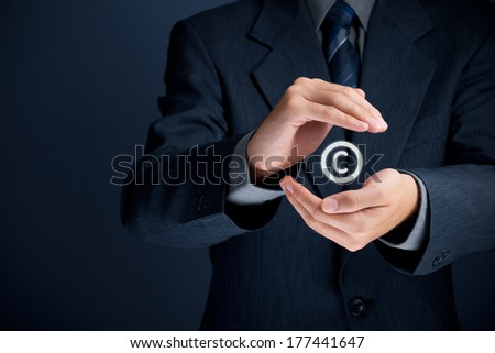 Copyright, patents and intellectual property protection law and rights. Author with protective gesture and copyright symbol.  - stock photo