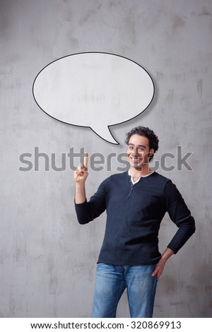 Copyspace in the bubble. Thoughtful arabic young man in casual wear pointing up while standing against grey background. - stock photo