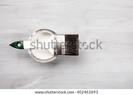 Copyspace with paintbrush and can with white paint lying on white wooden clean table. Top view. Copyspace. - stock photo