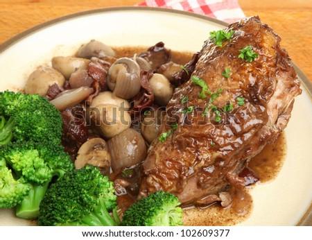 Coq au vin. Chicken casseroled in red wine. Focus on chicken breast. - stock photo