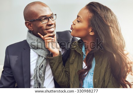 Coquettish young African American woman on a date with a handsome man playfully puckering up her lips for a kiss - stock photo