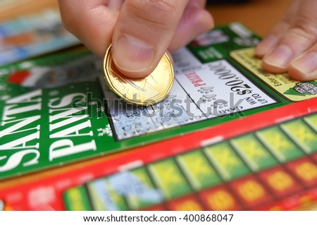 Coquitlam BC Canada - January 24, 2015 : Woman scratching lottery tickets. The British Columbia Lottery Corporation has provided government sanctioned lottery games in British Columbia since 1985. - stock photo