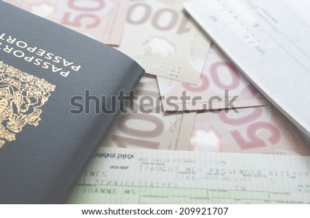 Coquitlam, BC, Canada - July 24, 2014 : Canada passport with boarding pass and money on the table.  All Canadian passports are issued by Passport Canada.  - stock photo