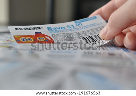 COQUITLAM, BC, CANADA - MAY 8 -  Coquitlam BC Canada - May 8, 2014 : Holding coupon for saving item. All coupons for Canadian store, they are issued by manufacturers of consumer packaged goods Canada. - stock photo