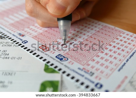 Coquitlam BC, Canada - October 09, 2014 : Close-up of woman hand marking number on 649 lottery ticket   - stock photo