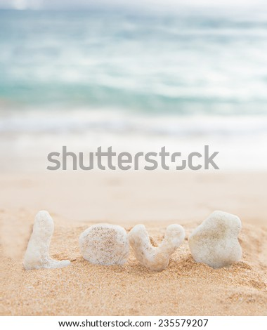 coral letters spelling the word love on a tropical beach - stock photo