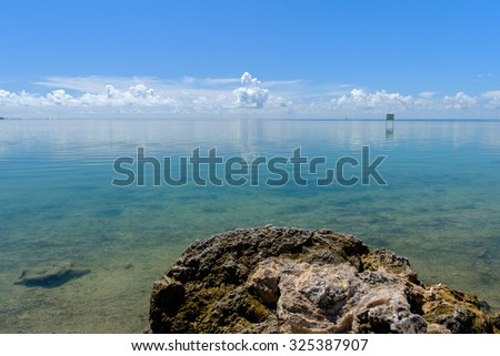 Coral rocks solidified along the shores of the shallow and crystal clear waters of the Florida Keys on a perfect day - stock photo