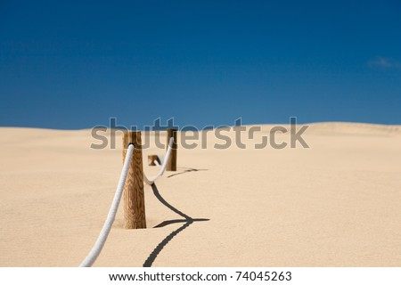 cord barrier on the beach with blue sky - stock photo