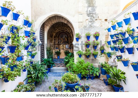 Cordoba, Andalusia Region, Spain. An old church with the traditional flowers set up of this town. - stock photo
