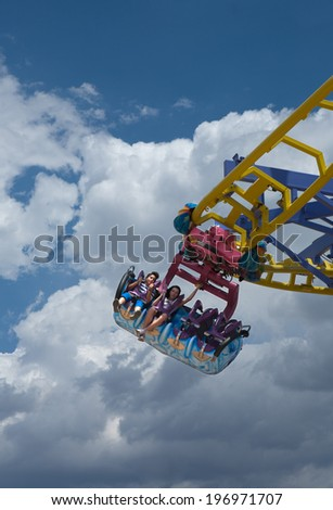 CORDOBA - MAY 31: Hanging roller coaster with people at funfair over cloudy sky. May 31, 2014 in Cordoba, Spain - stock photo