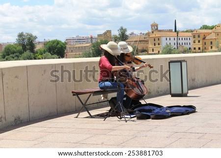 CORDOBA, SPAIN - MAY 22: Two young unidentified women busk under the Spanish sun on the Roman Bridge in Cordoba, also known as Cordova on May 22nd, 2014. - stock photo