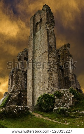Corfe Castle ruins in evening with dark stormy sunset sky - stock photo