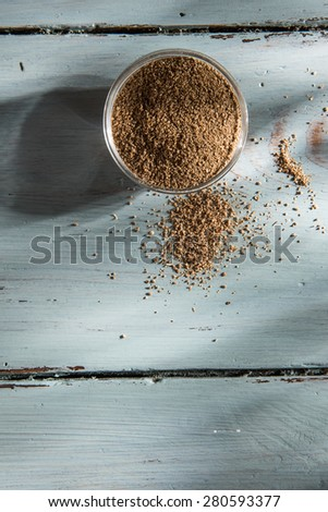 coriander powder in a bowl on wooden background - stock photo
