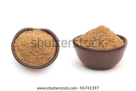 coriander powder in a clay bowl isolated on a white background - stock photo