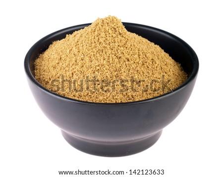 coriander powder on a ceramic bowl (isolated on white background) - stock photo
