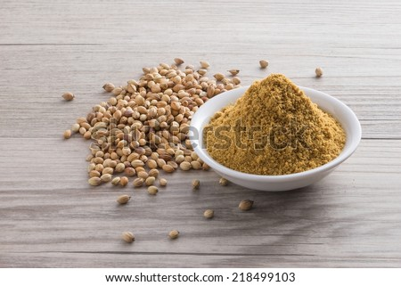 Coriander seed and powder on wooden texture background - stock photo