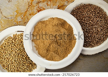 coriander seeds black and white in vintage enamelled plates ... - stock photo