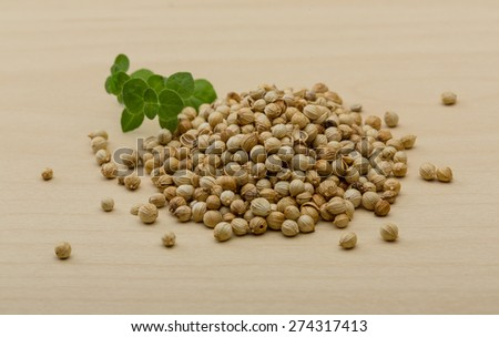 Coriander seeds heap on the wood background - stock photo