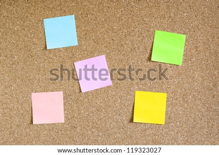 Cork board with colorful sticky notes - stock photo