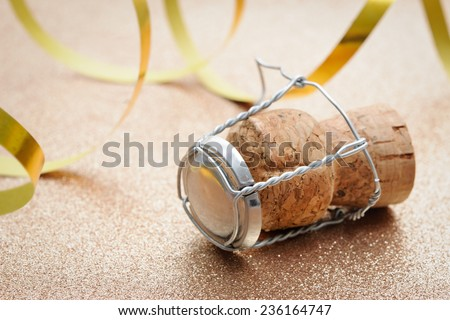 Cork from champagne bottle with streamers on golden background - stock photo