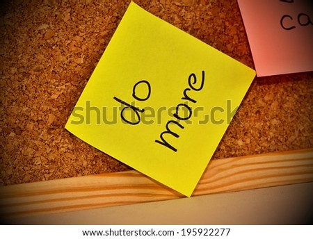 Cork notice board with sticky note pad with text do more - stock photo