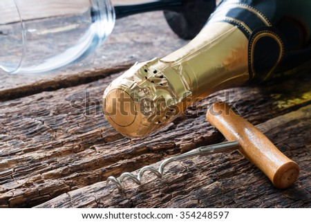 corkscrew and a bottle of champagne glass lying on the wooden background - stock photo