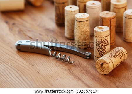 Corkscrew and corks on wooden table - stock photo